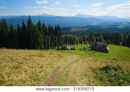 Hiking Trail To Small House In The Mountains. Wide Angle View Of Mountain Range And Valleys. View To