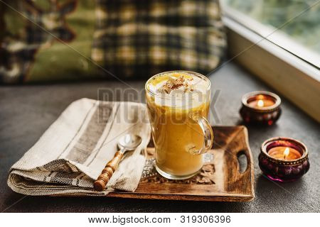 A Glass Cup Of Pumpkin Spice Latte Next To A Window