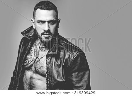 Handsome bearded man. In his brutal style. Brutal hispanic man. Bearded latino man with brutal tattoo on muscular chest. Brutal and athletic, copy space. poster