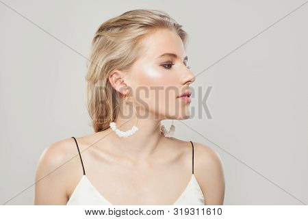 Pretty Woman With Blonde Hair, Makeup And Fashion Golden Earrings With Nacre On White Background. Pe