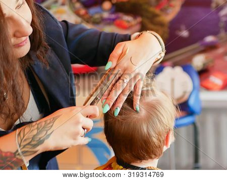 First Baby Haircut. Cute Blonde Toddler Is Happy To Be On A Haircut With A Professional Baby Hairdre