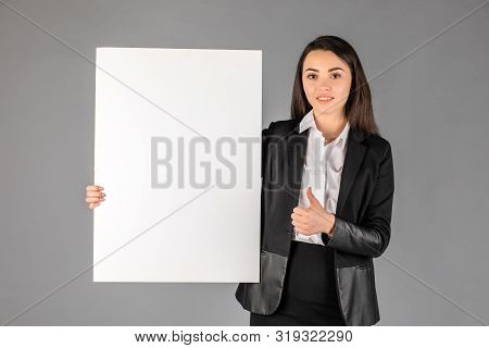 Young Smiling Woman Pointing At A Blank White Sheet For Advertisement On A Gray Background