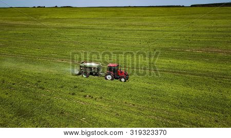 tractor rides on the field and makes inorganic fertilizers poster