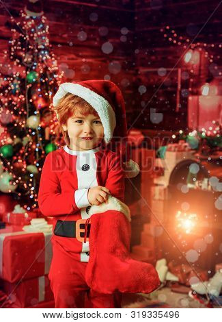 Merry Christmas And Happy New Year. Childhood Moments. Kid Boy Santa Hold Christmas Gift. Christmas