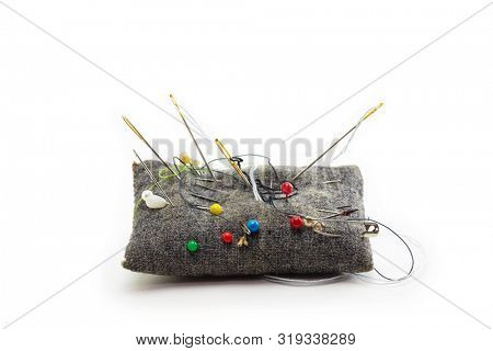 Pin cushion isolated on white. Well used grey pin cushion in real life condition, with needle and thread ends on white background.