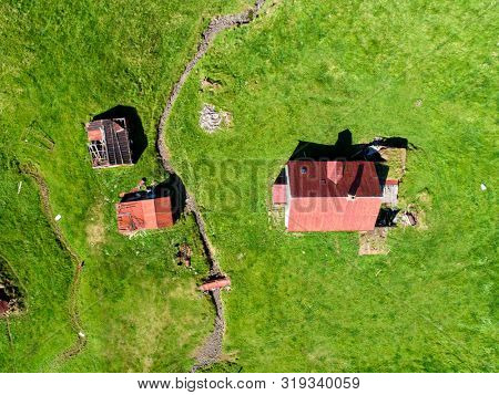 Aerial image of a derelict farmhouse and field in disarray
