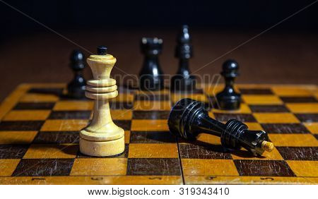 Defeated Black King Lying At The Feet Of The White Queen On The Chessboard Closeup