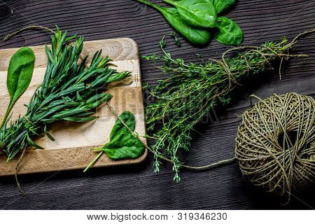 Bundle Of Sage And Thyme On Wooden Board Top View