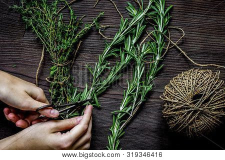 Thyme And Rosemary On Wooden Background With Hands Top View