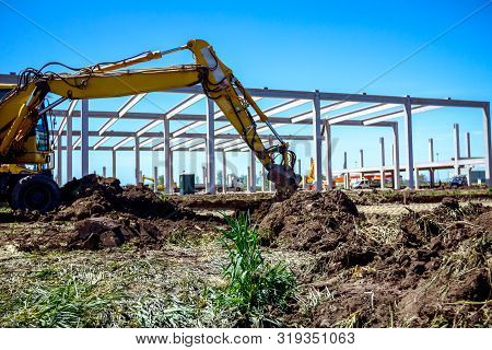 Big Excavator Is Excavating Soil At Construction Site, Project In Progress.