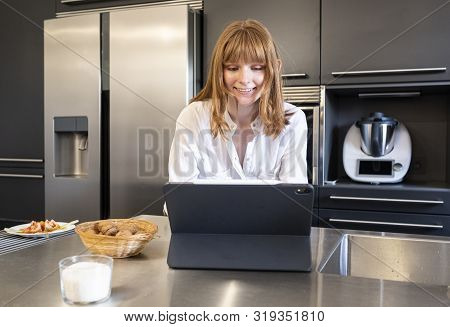 Young Russian Woman Looking At Laptop Computer In A Kitchen