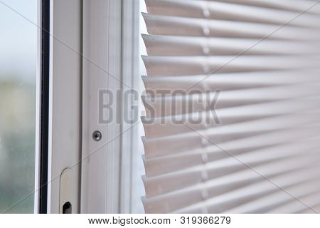 Closeup View Of Window With Horizontal Blinds. White Roller Blinds Or Louver Curtains At The Glass W