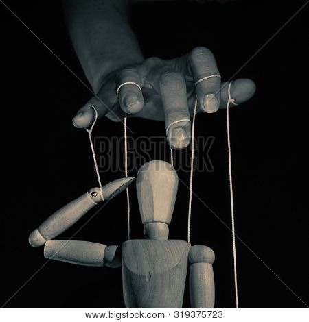 Concept Of Control. Marionette In Human Hand L, Black And White. Image.