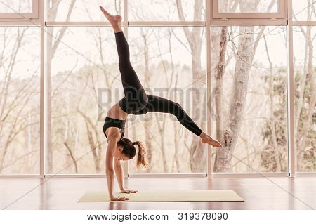 Side View Of Strong Young Lady In Sportswear Performing Handstand With Splits During Morning Yoga Ro