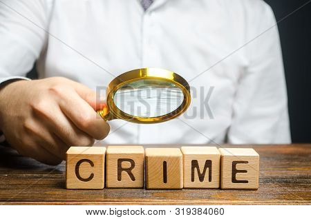 Man With A Magnifying Glass Examines The Word Crime. Investigation. Collection Evidence, Identificat