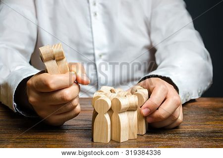 A Man Grabs A Figurine Of People From The Crowd. Hiring Employees. Market Segmentation And Niche Con