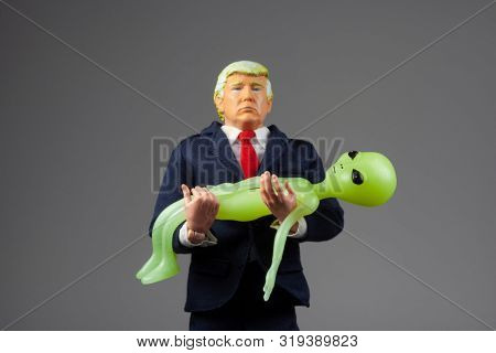 AUG 25 2019:  caricature of US president Donald Trump holding a grey space alien - Space Force concept