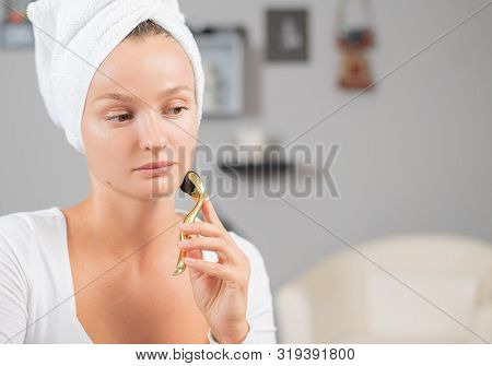Dermaroller for mesotherapy. Beautiful woman is using anti aging derma roller. Woman is making needles procedure on face using meso roller. poster
