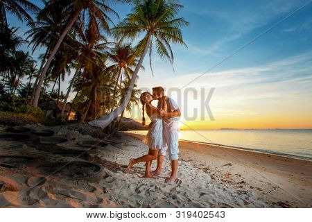 couple hugging at sunset on a tropical beach