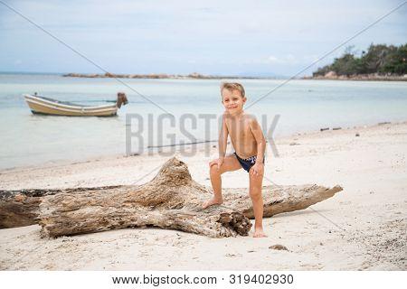 little boy sitting on the beach
