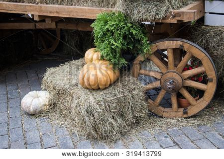 Orange Pumpkins On Hay Decoration Cartwheel Background . Autumn Street Decoration. Rural Market Atmo