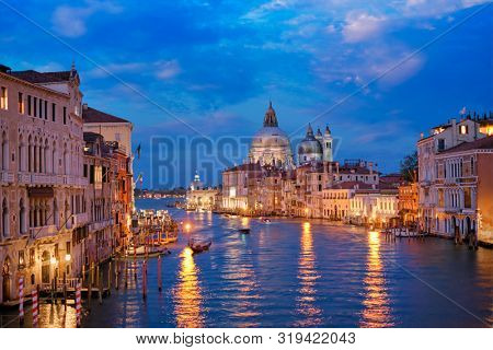 View of Venice Grand Canal with boats and gondola and Santa Maria della Salute church in the evening from Ponte dell'Accademia bridge. Venice, Italy