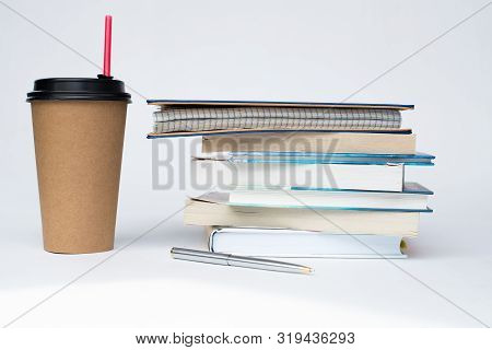 A Paper Cup Of Coffee With A Red Straw Stands Next To A Stack Of Books On A White Background