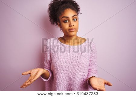 Young african american woman wearing winter sweater standing over isolated pink background clueless and confused with open arms, no idea concept.