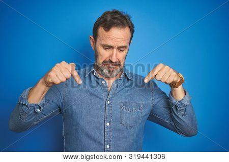 Handsome middle age senior man with grey hair over isolated blue background Pointing down looking sad and upset, indicating direction with fingers, unhappy and depressed.