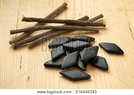 Heap of dried Licorice roots and black salt licorice confectionary, a Dutch treat