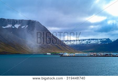 Isafjordur, Iceland, The Village And The Bay Seen From The Sea With The Snowy Mountains In The Backg