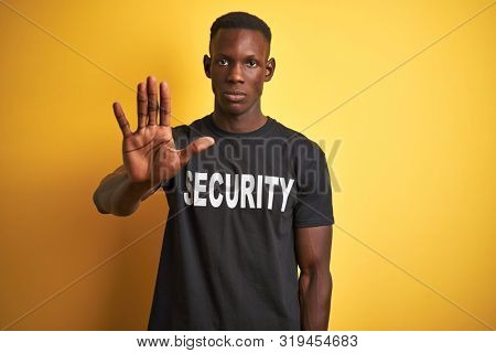 African american safeguard man wearing security uniform over isolated yellow background doing stop sing with palm of the hand. Warning expression with negative and serious gesture on the face.