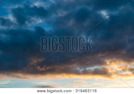 Blue dramatic sunset sky background - colorful sky clouds lit by sunlight. Vast sky landscape panoramic scene, sunset sky evening view