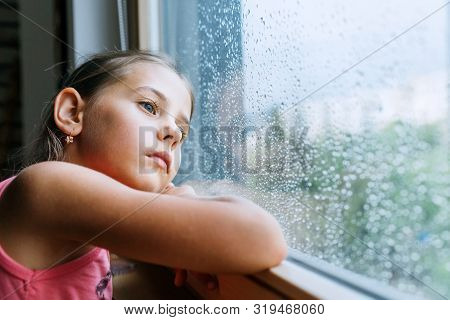 Little Sad Girl Pensive Looking Through The Window Glass With A Lot Of Raindrops. Sadness Childhood