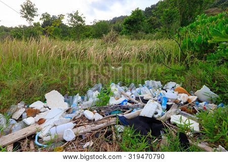 Important plastic pollution in a green pure meadow near a beach shore in Thailand