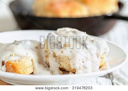 American Biscuits From Scratch Covered With Thick White Sausage Gravy. Selective Focus With Cast Iro