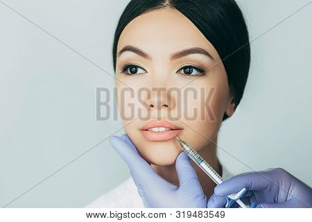 Asian Woman Plumper Lips, Getting Bigger Lips. Prick Of A Syringe For The Lips. Injections For Bigge