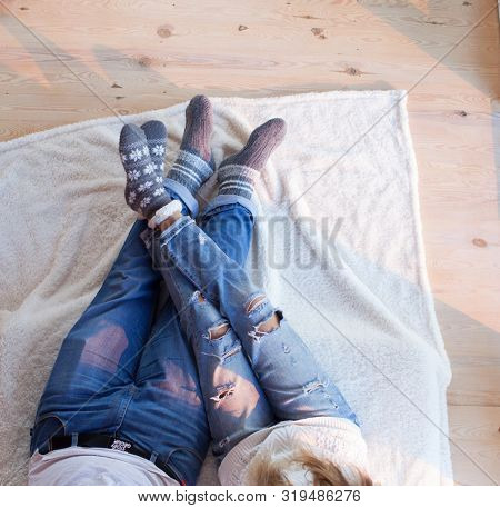 Couple in love wearing distressed jeans and thick socks sitting on the floor