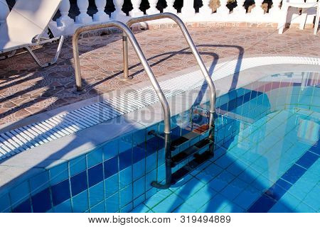 Handrail On The Pool. Swimming Pool With Stair Closeup. Pool Handrails View. Water Swimming Pool Wit