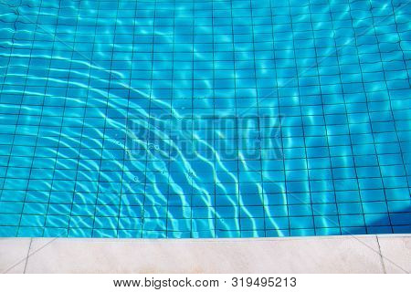 Blue Ripped Water In Swimming Pool. Swimming Pool Bottom Caustics Ripple And Flow With Waves Backgro