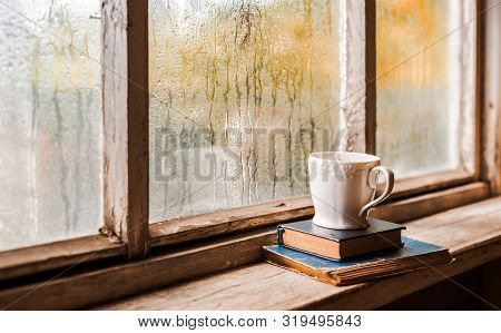 A White Cup And Old Books On The Background Of A Rustic Wooden Wet Window, Copy Space. Hot Drink For