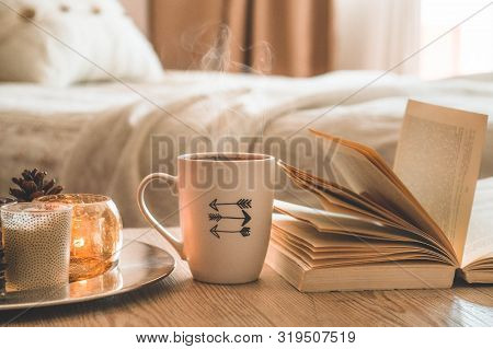 Book, Cup Of Coffee And Many Candles On The Home Background.  Home And Home Decor. Candles Flame. Ho