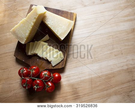 Wooden Table With Parmesan Cheese And Tomatoes. Healthy Food. Wooden Drska With Parmesan. Italian Fo