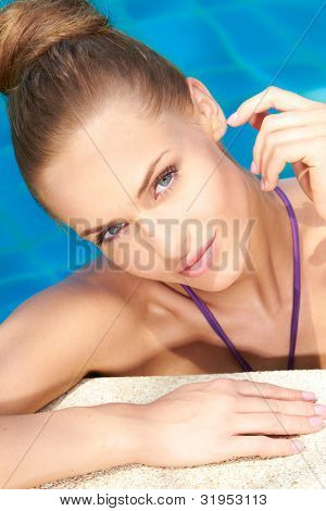 Close up of young adorable woman in swimming pool