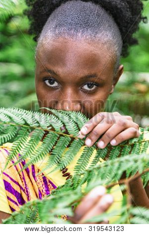 African Woman Hid Behind Green Leaves In Jungle
