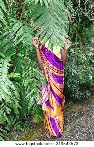 African Woman Hid Behind Green Tree In Park