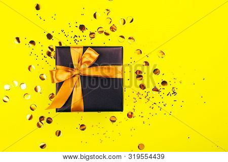 Black Gift Box With Golden Bow On Yellow Background With Glitter. Holiday Concept.