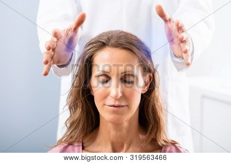 Close-up Of A Therapist Hand Giving Reiki Healing Treatment To Woman In Spa