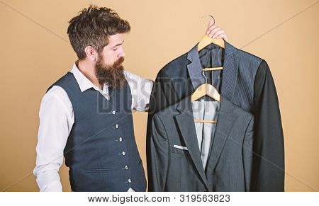 Being A Tailor. Mens Tailor. Hipster Holding Tailor Made Coats At Department Store. Bearded Man Choo