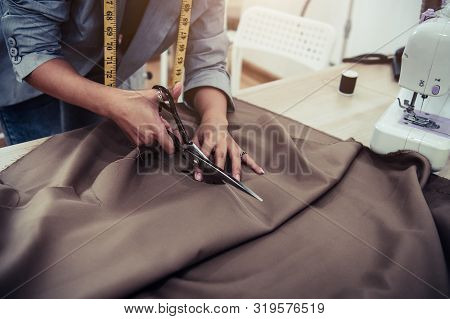 Dressmaker Cutting Dress Fabric On Sketch Line With Sewing Machine. Fashion Designer Tailor Or Sewer